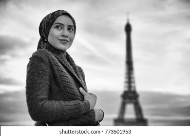 Young beautiful Muslim hijab woman in Paris with Eiffel Tower in background