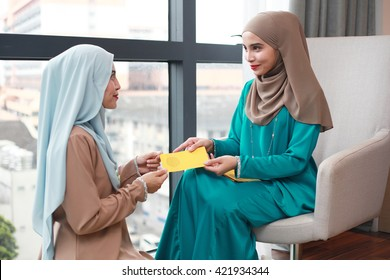 Young Beautiful Muslim Woman in head scarf with modern clothes received raya packets during hari raya aidilfitri festival