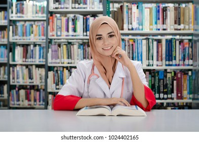 Young and beautiful Muslim's doctor reading some books in library.