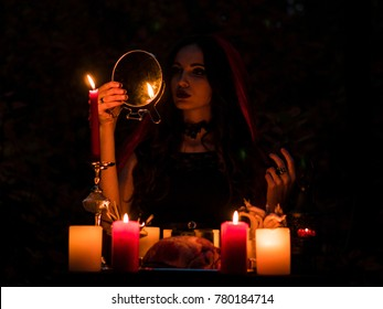 Young beautiful and mysterious Witch woman Provide Dark Ritual in woods With Detached Heart and Candles Looking in the Mirror
