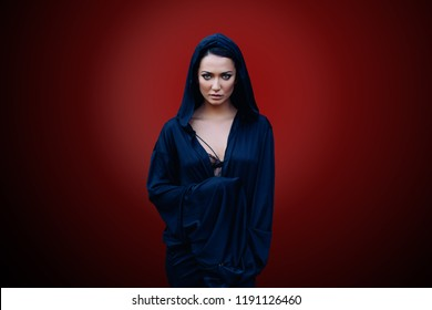 Young beautiful mysterious woman with a black hair and in the dark blue cloak with hood at the red background
