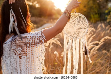 Young Beautiful And Mysterious Woman Holding Dreamcatcher In field.