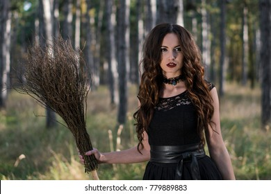 Young beautiful and mysterious woman Walking with Broom in woods, in black Dress