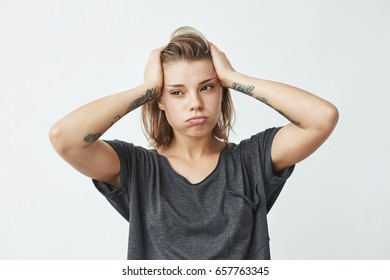 Young beautiful nervous upset girl thinking holding head over white background.