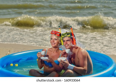 A young and beautiful newly-married couple enjoying on the beach in swimming pool with cups of coffee