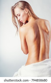 Young beautiful nude woman back on white background