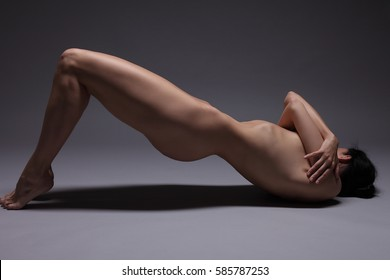 Young beautiful nude woman practicing yoga on a dark background