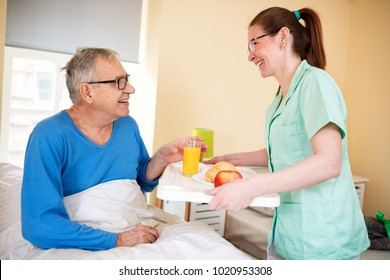 Young beautiful nurse brings breakfast to patient at nursing home