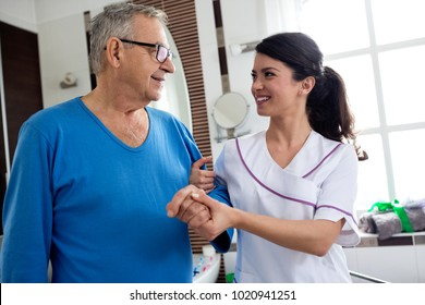 Young beautiful nurse helps to senior man at bathroom nursing home