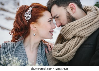 Young beautiful pair of bride and groom embrace on a background of a winter landscape