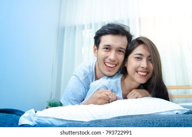 Young beautiful pair of lovers  relaxing on the bed hug and smiles with camera