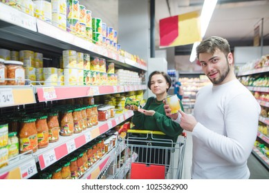 Young beautiful pair posing in a supermarket with products in their hands. A young man and a girl buy canned vegetables in a supermarket