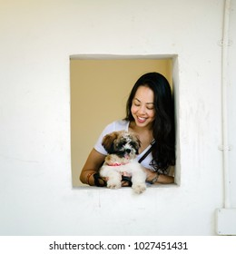 A young and beautiful pan Asian woman is carrying her dog and is having her picture taken in a square window in the day. The dog is small and cute and she is smiling and relaxed.