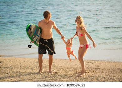 Young and beautiful parents playing with his daughter on the beach