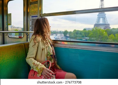Young beautiful Parisian woman traveling in a subway train, sitting near the window and looking at the Eiffel tower