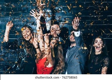 Young beautiful people dancing in confetti. Party fun. New year, Birthday, Holiday Event concept