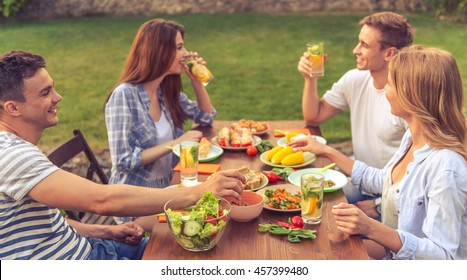 Young beautiful people are talking, eating, drinking and smiling while sitting at the table and having picnic outdoors