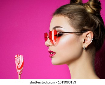 Young beautiful playful woman holds heart shaped lollipop. Valentines day, love or theme party concept. Smokey eyes and pink lips makeup. Studio shot