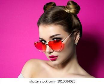Young beautiful playful woman looks over her heart shaped red glasses. Valentines day, love or theme party concept. Smokey eyes and red lips makeup. Studio shot