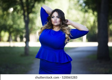 Young beautiful plus size model in blue dress outdoors, xxl woman on nature, professional makeup and hairstyle