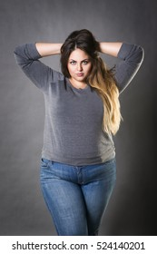 Young beautiful plus size model in blue jeans, xxl woman on gray studio background