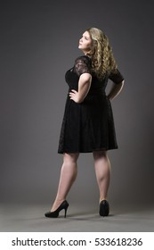 Young beautiful plus size model in black dres, xxl woman on gray studio background, full length portrait