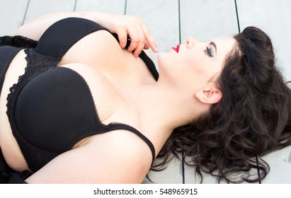 Young beautiful plus size model with big breast in black bra, professional makeup and hairstyle lying on the wooden background, xxl woman