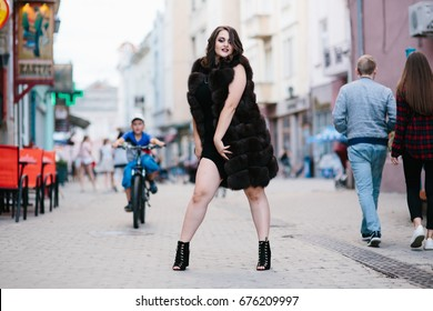 Young beautiful plus size model in black dress and luxurious fur coat dress outdoors, xxl women on nature, professional makeup and hairstyle
