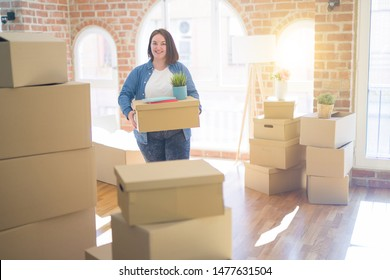 Young beautiful plus size woman moving to a new house, holding cardboxes smiling very happy for new apartment