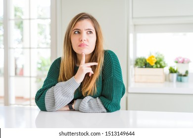 Young beautiful plus size woman wearing casual striped sweater Thinking concentrated about doubt with finger on chin and looking up wondering