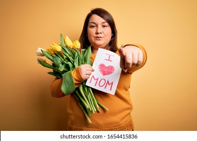 Young beautiful plus size woman celebrating mothers day holding love mom message pointing with finger to the camera and to you, hand sign, positive and confident gesture from the front
