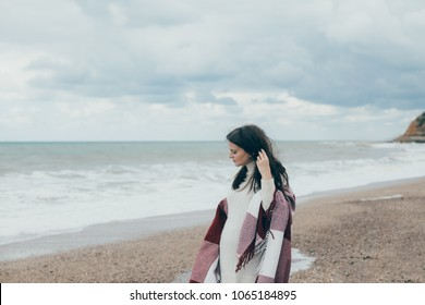 Young beautiful pragnant woman in a white knitted sweater posing near sea at the beach