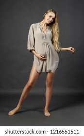 Young beautiful pregnant leggy blonde woman wearing a short light dress smiling posing on a gray background. Studio photo. Maternity, lifestyle, fashion. Advertising and commercial design. Copy space.