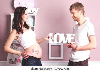 Young beautiful pregnant woman and her handsome husband showing a love message. Pregnant woman 5 month. Love concept.