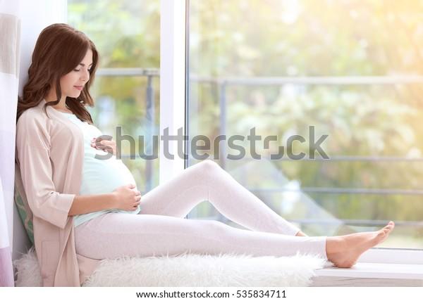 Mladá krásná těhotná žena sedí na parapetu doma