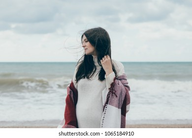 Young beautiful pregnant woman in a white knitted sweater posing near sea at the beach