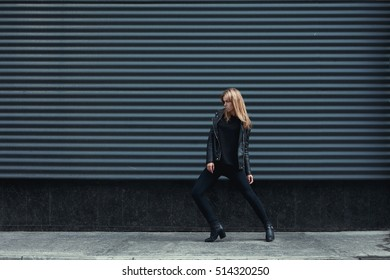 Young beautiful pretty blonde european girl walking along the street wearing black leather jacket, black jeans. Dark metal background. Trendy, Urban street style. Autumn Vogue Style. Toned ifilters
