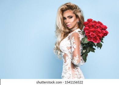 Young beautiful pretty girl standing and holding bukiet  with red roses. Vogue fashion style studio portrait of sexy girl in white elegant dress standing in studio - Image