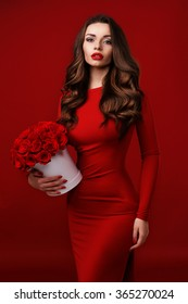 Young beautiful pretty girl standing and holding white box with red roses. Vogue fashion style studio portrait of sexy girl in red dress