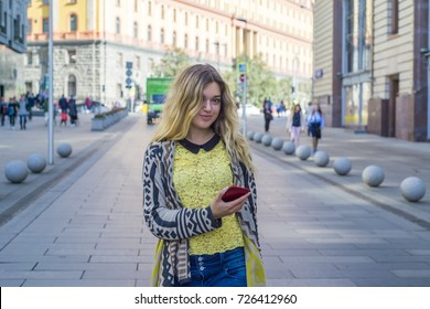 Young beautiful pretty girl walking along the street with phone in hand