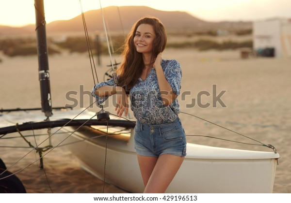 Young beautiful pretty girl wearing blue blouse and jeans shorts standing near sailing catamaran at sandy beach. Outdoor summer portrait with lovely soft sunset backlght. Smiling woman looking at you.