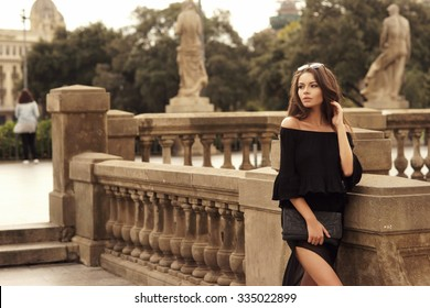 Young beautiful pretty woman walking at old city center and looking away. Stylish girl in black blouse and skirt posing outdoors