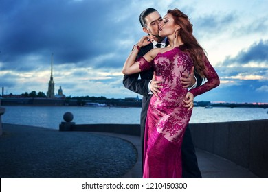 Young, beautiful and professional couple dancing tango on the quay of the river at daybreak in Saint-Petersburg on Peter and Paul Fortress and Neva river background