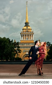 Young, beautiful and professional couple dancing tango in Saint-Petersburg of the Admiralty building background at daybreak
