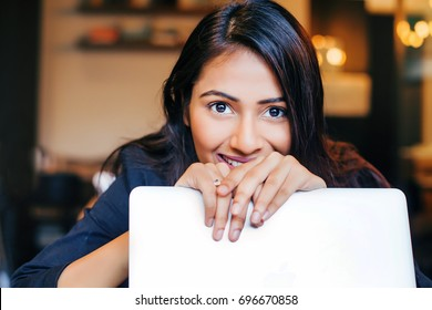 A young beautiful professional Indian woman smiling and looking over her laptop