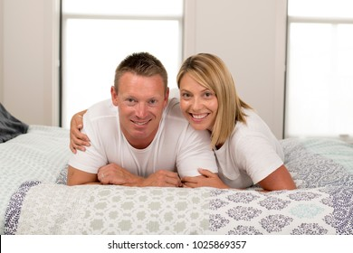 young beautiful and radiant couple 30 to 40 years old smiling happy posing sweet and cuddle lying on bed at home bedroom in successful husband wife relationship concept
