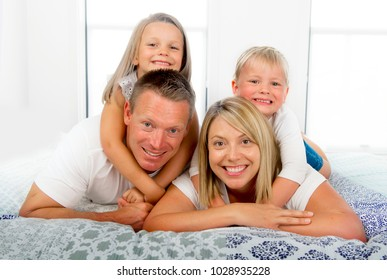 young beautiful and radiant couple 30 to 40 years old smiling happy posing sweet lying on bed with little son and beautiful daughter at home bedroom in love family concept