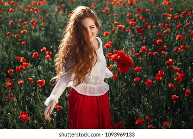 Young beautiful readhead woman with freckles walking and dancing through a poppy field at sunset