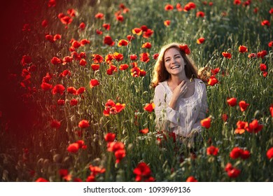 Young beautiful readhead woman with freckles in a poppy field