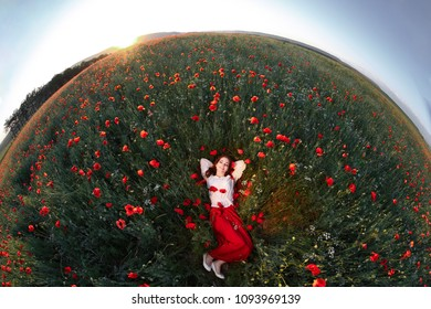 Young beautiful readhead woman with freckles lying in a poppy field